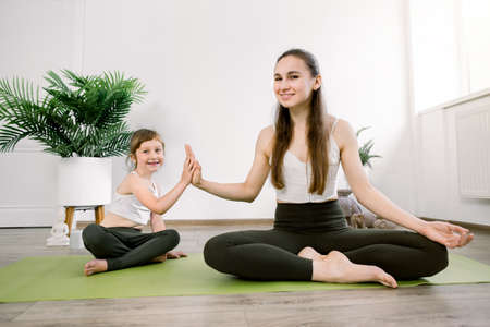Young mother and cute daughter, doing yoga sports exercises at home, have fun and spend a good time together, sitting in lotus position and giving high five. Concept of a healthy lifestyle