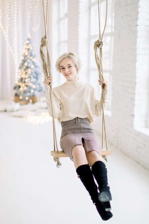Young charming smiling blond girl in trendy warm clothes, swinging on the wooden swing in beautiful light decorated room with Christmas tree and big windows on the background 免版税图像