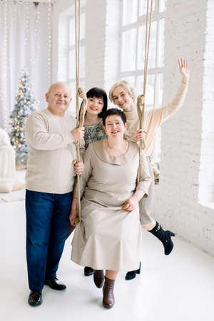 Christmas, winter holidays, family togetherness. Smiling middle aged mom sitting on swing, dad and two young pretty sisters, having fun while celebrating holidays at beautiful light decorated hall.