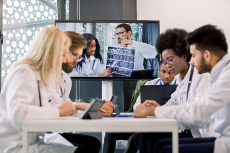 Multiracial doctors having a video conference at light office with two African and Caucasian doctors holding CT, sitting at the table and interacting each other, using tablets, laptop and making notes