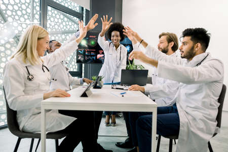 Group of motivated international doctors or scientists, sitting around the table in conference room at modern clinic, giving a high fives gesture with their hands, after great teamwork 版權商用圖片