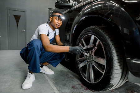 Professional African male worker in overalls and black protective gloves, cleaning alloy wheels rims of luxury car with a special brush for cast wheels in a detailing workshop, looking at camera Stockfoto