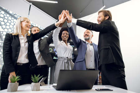 Happy multiracial entrepreneurs in formal wear in business office, giving high fives to each other as if celebrating success, unity or starting new project. High-five for success