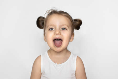 Close up head shot portrait of happy little adorable blond positive girl with ponytails, showing tongue, funny grimace, teasing, playing, looking at camera, isolated on white studio background