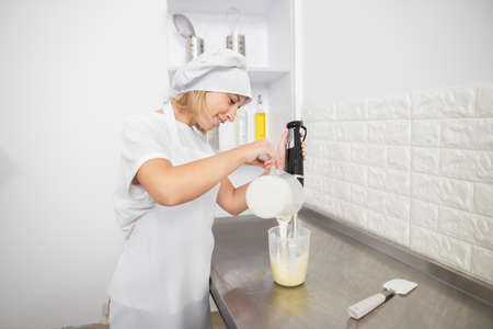 Cooking, baking and people concept. Young woman, professional confectioner, working in the kitchen, preparing the sauce or ganache for desserts, pouring cream from one cup to another