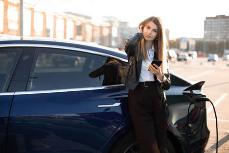 Young nice-looking successful business lady with long har, wearing black formal wear and white shirt, looks at camera while waiting for her electric car refueling