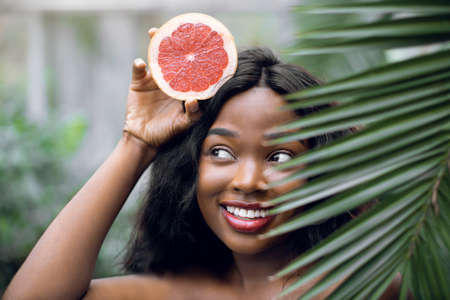 Close up portrait of young emotional beautiful afro american woman with grapefruit in her hands, looking out of green plam leaf indoors in greenhouse or garden. Summer and beauty concept. Stock Photo