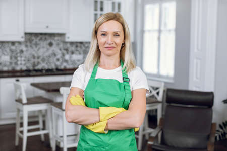 Portrait of woman in green apron and yellow gloves
