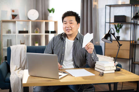Smiling asian freelancer playing with paper plane Foto de archivo