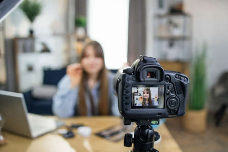 Popular caucasian blogger testing new cosmetics for advertisement during live broadcast. Young woman sitting at table and looking at camera that fixed on tripod. Banque d'images