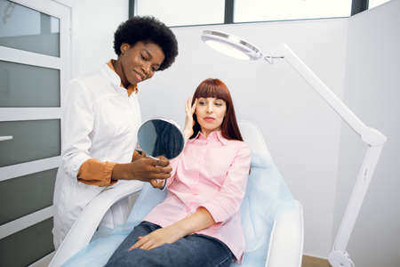 Female African doctor cosmetologist is consulting woman client who looking at mirror in beauty clinic. Beautician preparing patient to skin care procedure in spa salon, talking about skin treatment