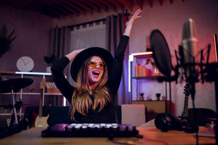 Happy woman in stylish hat and glasses holding hands up and mouth open while sitting at music studio. Female artist feeling satisfaction of new recorded song.