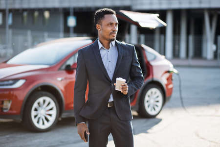 Handsome african man in business suit drinking fresh coffee while waiting for modern electric car to be charged. Young male holding smartphone in hand, standing outdoors and looking aside.