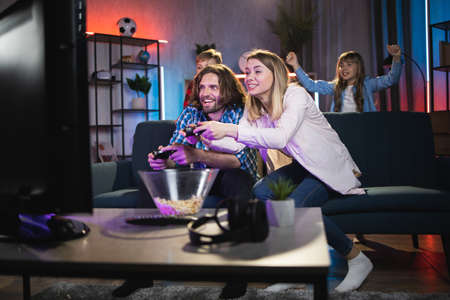 Young man and woman sitting on couch and emotionally playing video games. Excited son and daughter standing behind and cheering their parents. Entertainment at home.