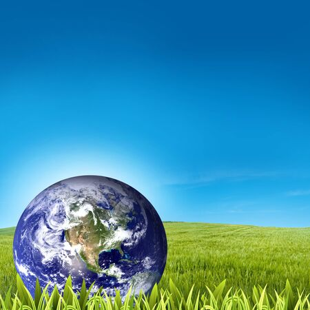 Globe on green grass with blue sky background