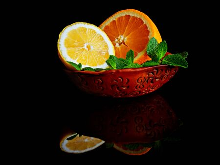 Citruses lemon and orange with mint in a ceramic bowl