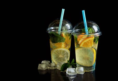 Two glasses of lemonade isolated on a black background.
