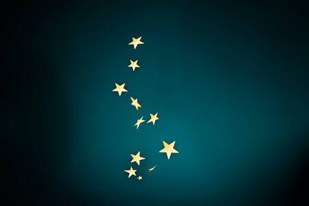 Confeti de estrellas doradas de moda cayendo sobre fondo degradado azul oscuro. Foto de archivo