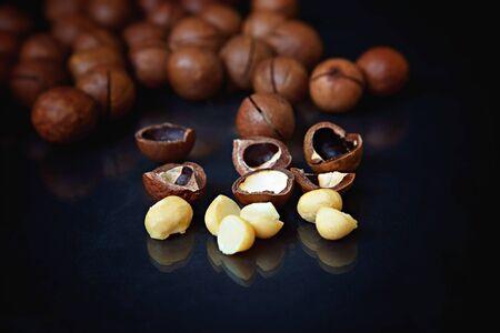 Peeled and unpeeled macadamia nuts on a black background