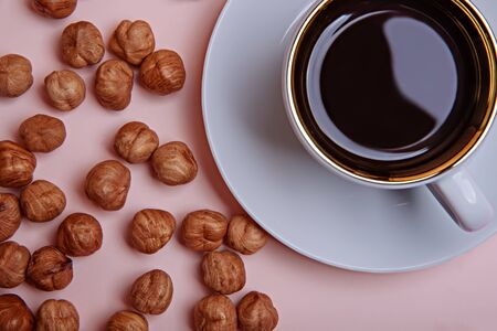 A cup of espresso coffee on a saucer and peeled hazelnuts on a coral pink background. View from above. Flat lay.