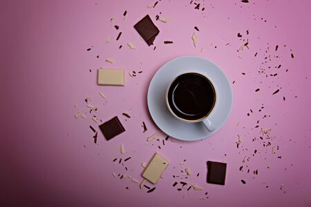 A cup of espresso coffee, pieces and crumbs of dark and white chocolate on a pink background. Flatlay. View from above.