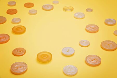 Buttons of pastel colors pink, beige, white, pearl on a yellow background.
