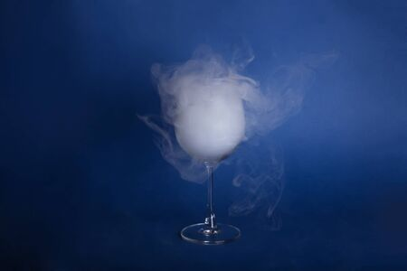 Large wine glasses with smoke on a blue background. Color of the year 2020, Classic Blue.