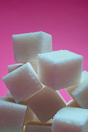 Sugar cubes on a bright pink background. Macro photo. Archivio Fotografico