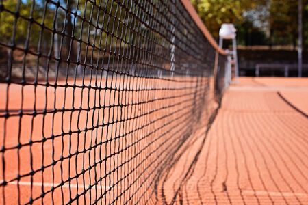 Tennis net on the outdoor court. Blurred background. Coral tones. Midday lighting.