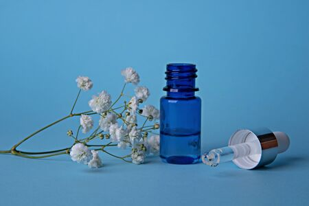 Cosmetic serum. Dropper with a drop and a bottle on a blue background. Copy space. Place for text.