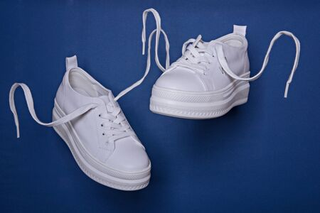 Flying in the air white sneakers on the classic blue background. Abstract surrealism and minimalism shopping concept. Archivio Fotografico