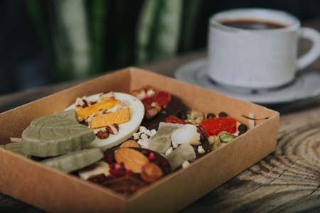 Chocolates with dried fruits in a craft box and a cup of espresso coffee.