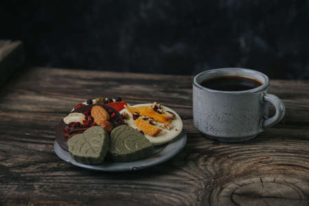 Chocolates with dried fruits and a cup of espresso coffee.