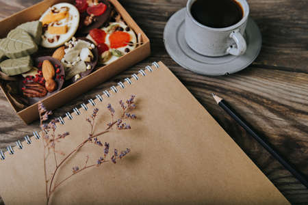 Chocolates with dried fruits in a box and craft paper notebook near the cup of coffee. Place for your text.