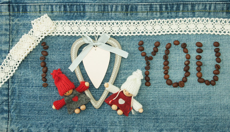 Valentine, greeting card with wooden white heart,coffee beans and knitted loving couple man and woman.