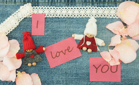 Valentine, greeting card with knitting couple in love and soft pink rose petals.
