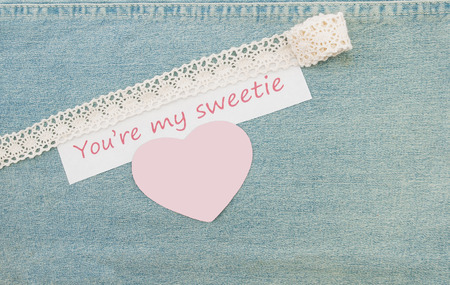 Valentine greeting card with blank heart and lettering You're my sweetie on the denim background.