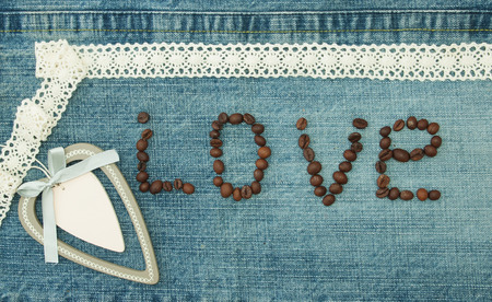 Valentine, greeting card with wooden white heart and coffee beans. Фото со стока