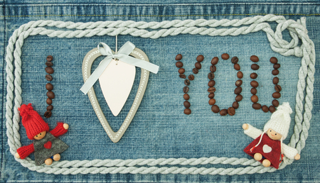 Valentine, greeting card with wooden white heart, coffee beans and knitted loving couple man and woman.