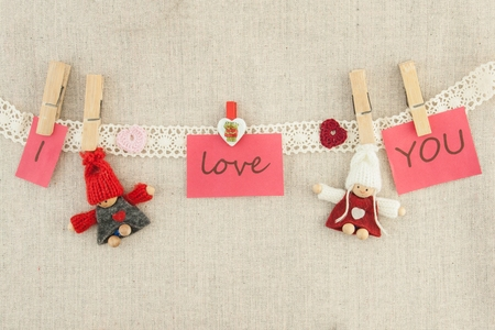 valentine, greeting card. Wooden pins, red and pink hearts, knitted loving couple man and woman Фото со стока