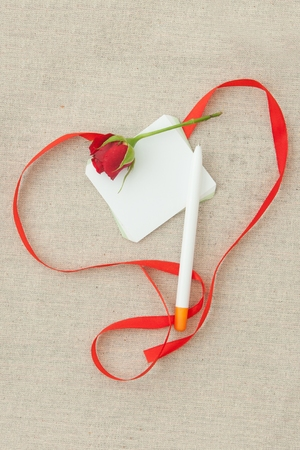 Valentine, greeting card with red little rose, pen, blank and red ribbon in the shape of a heart. Фото со стока