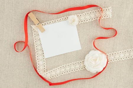 Valentine, blank, greeting card with red ribbon, white roses and pin.