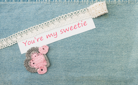 Valentine greeting card with three crocheted pink hearts and  lettering You%u2019re my sweetie on the denim background.