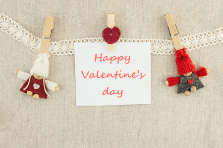 Valentine, greeting card. Wooden pins, knitted loving couple man and woman, red heart