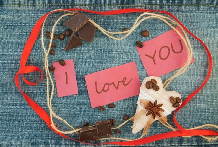 Valentine, greeting card with  brown coffee hearts, red ribbon, coffee, chokolate on the denim background. Handmade concept. Lettering I love you
