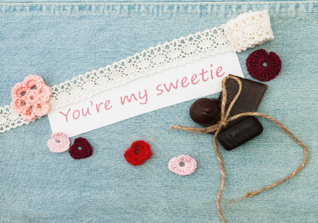 Valentine greeting card with pink and red hearts, flower, chokolate and lettering You're my sweetie on the denim background