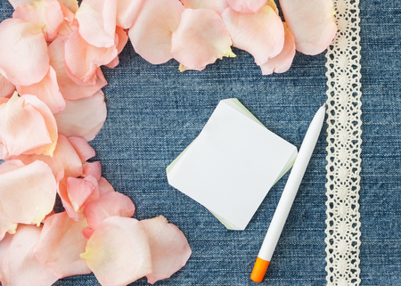 Valentines day  background. Denim blue background with soft pink rose petals, paper and pen.