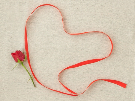 Valentine, greeting card with red little rose and red ribbon in the shape of a heart. Фото со стока