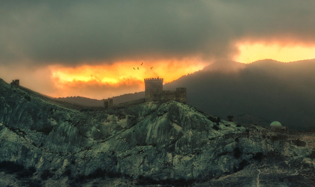 panorama, horizontal eerie burning view of Crimean mountains with rocky coastline, Genoa fortress, crow before the rain, storm, tornado.Toned.