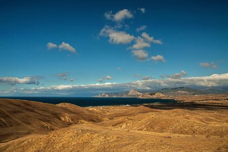 panorama, horizontal view of Crimean mountains with rocky coastline in the foreground , blue sky and  Black sea.